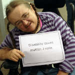 """Woman with a disability holding a sign that says """"Disability Issues Matter. I Vote."""""""