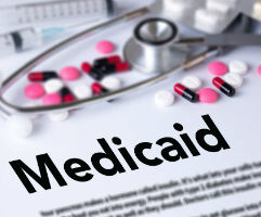 Document with medicaid as heading, stethoscope laying and pills scattered on top.