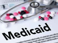 Document with medicaid as heading, stethoscope layin on top with pills spilled on top.