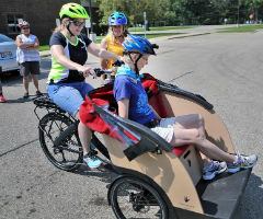 Carolyn Brandeen rides in the front as Cathy Blackburn begins to pedal an electronically assisted three-wheeled bike during a training session in Janesville.