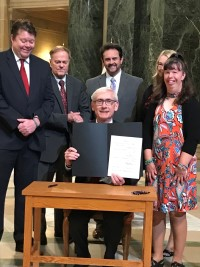 Governor Evers holding up signed bill sitting at table surrounded by people standing