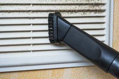 Closeup of vacuum cleaner pipe and ventilation grill