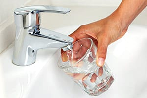 Glass being filled with hard water from a home faucet