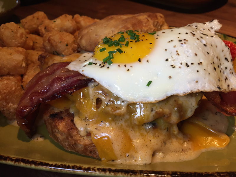 A freshly made biscuit is topped with buttermilk fried chicken, cheddar, applewood bacon, sausage gravy and a sunnyside up egg - Jimmys Famous American Tavern