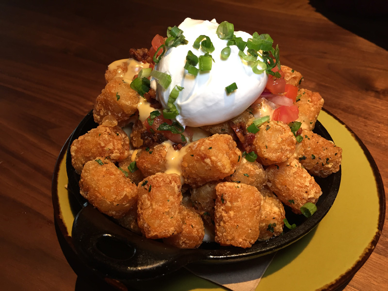 Cross between tater tots and nachos with sour cream and salsa fresca - jimmys fat