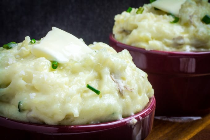 Creamy, buttery Yukon gold potatoes are mashed together with garlic and sharp Parmesan cheese in these Creamy Garlic Parmesan Mashed Potatoes. These potatoes are perfect for your Thanksgiving table, but so easy that you'll want to make them all year round. Top with chives and serve with an extra sprinkle of Parmesan cheese and butter for the perfect holiday side dish.