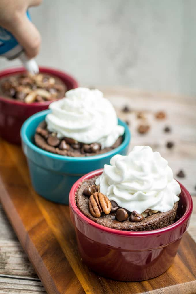 Rich chocolate cake made in less than 2 minutes! This Gluten Free Chocolate Mug Cake is bursting with smooth chocolate chips and crunchy pecans. So easy to make, this chocolate mug cake is made in your favorite coffee mug or small baking dish, and only takes a minute and a half in the microwave before it's finished. Gluten free baking has never been easier!