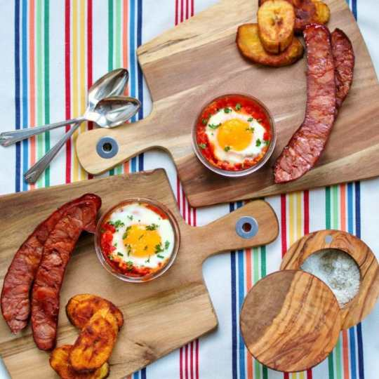 A Cuban style breakfast of eggs coddled in spicy tomato sauce, grilled chorizo, and fried plantains. #Cuban #Breakfast #eggs