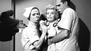 Screenshot from Twilight Zone. Two pig-faced nurses restrain a blonde woman.
