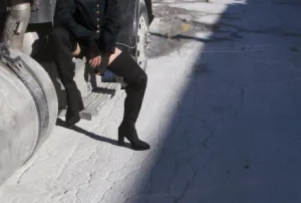 A model shown from the waist down wearing black thigh high Syro shoes.