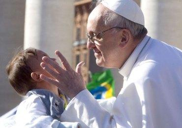 papa francesco si ferma a salutare e baciare un bambino prima della messa a san pietro