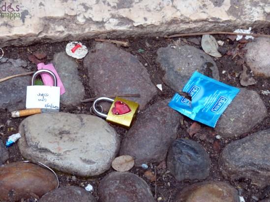 lucchetti d'amore e preservativi sul ciottolato nel cortile della casa di giulietta
