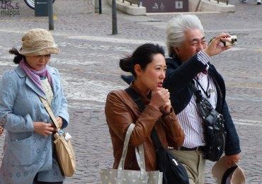 La foto camminando contro vento turista asiatico in piazza bra a verona