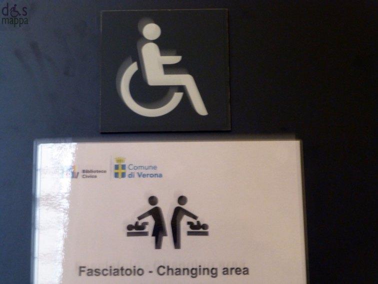 simbolo disabili e fasciatoio sulla porta biblioteca civica di verona