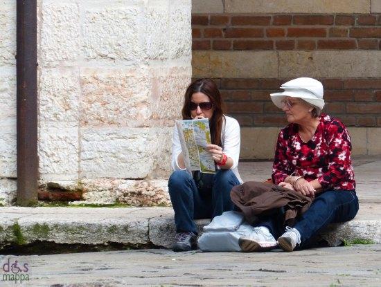 Turiste studiano la mappa turistica di Verona sedute in Cortile Mercato Vecchio