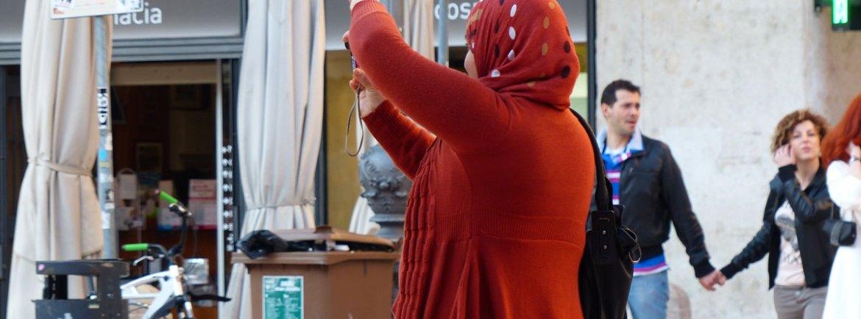 Turista vestita di rosso con velo che fotografa Piazza delle Erbe a Verona