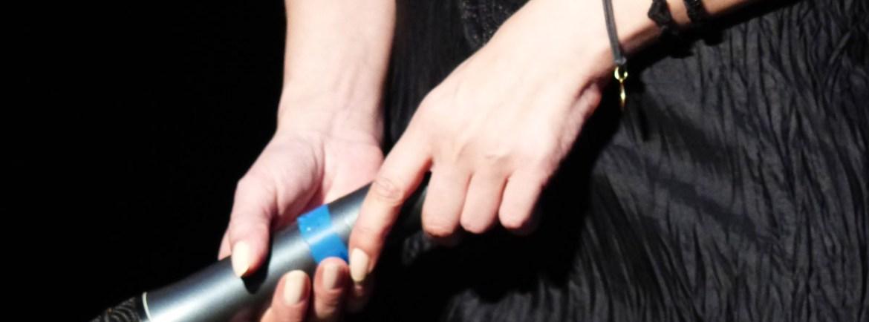 Le mani di Elisabetta Fadini con microfono sul palco di Rumors Festival al teatro romano