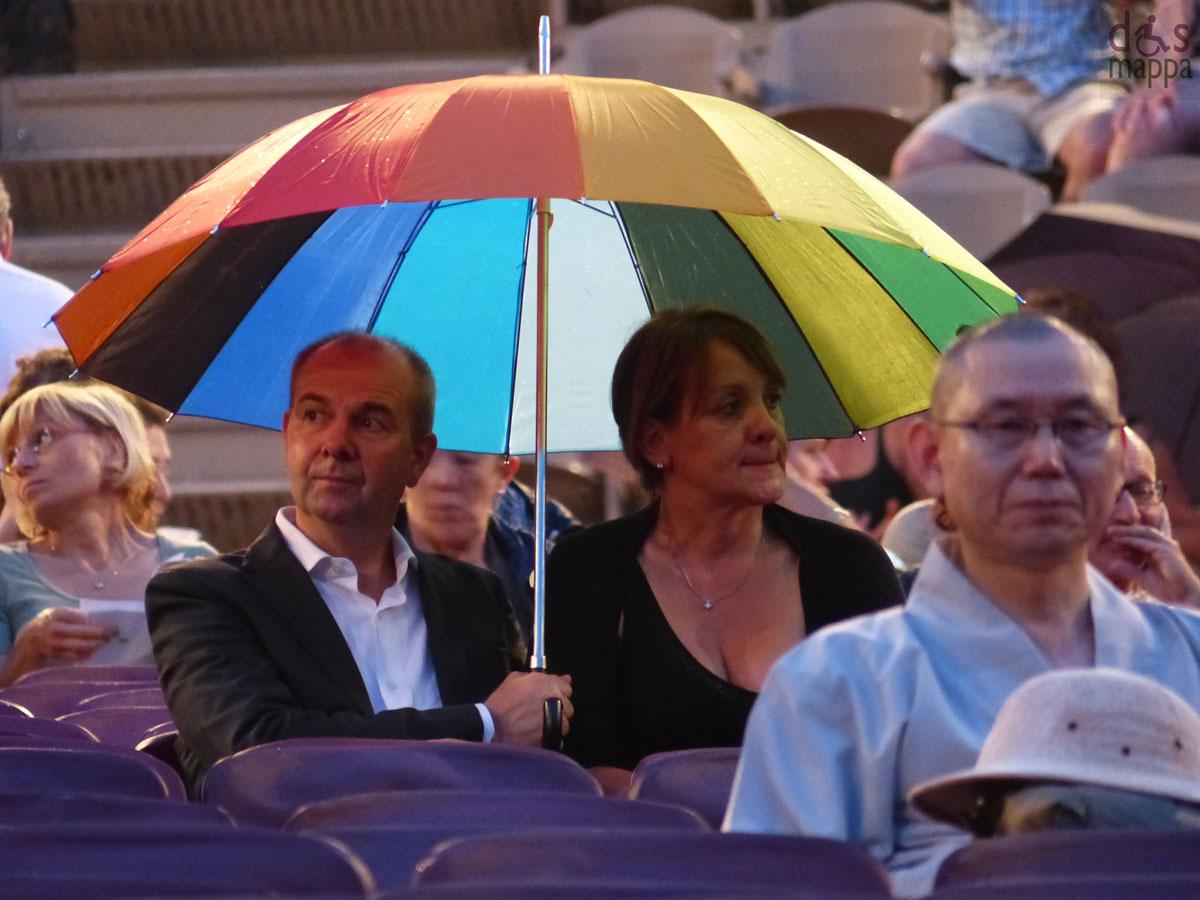 coppia con ombrello arcobaleno e spettatore asiatico In occasione del Bicentenario Verdiano l'Arena di Verona celebra il maestro con la Messa da Requiem, suonata da Orchestra e Coro della Fondazione Arena di Verona e Orchestra e Coro della Fondazione La Fenice di Venezia.