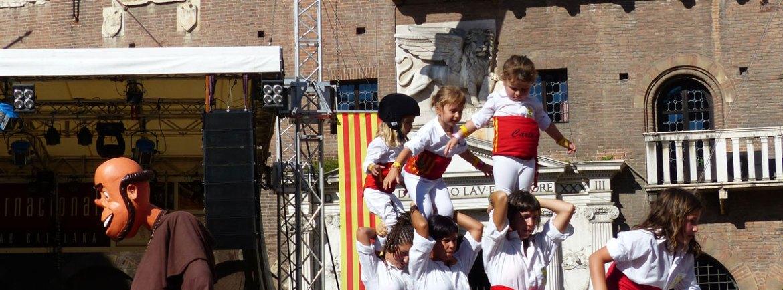 """Folklore e cultura catalane saranno i protagonisti di queste due giornate dedicate allo scambio culturale e alla conoscenza del popolo catalano.Più di 500 artisti appartenenti a ventuno gruppi venuti da differenti zone della Catalunya, offriranno le loro musiche, balli e giochi tradizionali e nel frattempo sfileranno con i ricchi e sfarzosi elementi popolari come i Gegants i capgrossos, la mulassa e i dracs.L'Aplec Internazionale, irresistibile momento di festa e musica, inizierà venerdì 2 agosto e raccoglierà il pubblico in Piazza delle Erbe, dove un coinvolgente spettacolo di danze catalane e torri altissime di uomini darà inizio alla festa. I castellers (torri umane) sono stati dichiarati dall'UNESCO Patrimonio Culturale Immateriale dell'Umanità.A seguire, un concerto unico nella chiesa di Sant'Anastasia, dove parteciperà una Cobla (formazione orchestrale tipica della Catalunya), la Polifonica de Puigreig (corale di 35 componenti) e l'orchestra Dodekachordon (composta da 19 musicisti) darà vita ad un unica fusione di ritmi e note.La tradizione continuerà a ballare anche Venerdì sera durante un incontro musicale e di danze che vedrà partecipare l'ensemble FolkBanda con le note venete tradizionali e gli artisti catalani; un mix di musiche e di identità culturali ritmerà i minuti di questa incredibile festa catalana. Faranno parte del clima di festa anche le Havaneres, canzoni e musica tradizionale che i marinai catalani portavano dai loro viaggi a Cuba, il tutto accompagnato dal """"ron cremat"""" (rum flambée) che spegnerà le luci della prima notte dal sapore marinaio.La giornata di sabato 3 agosto continuerà con momenti di danza e coinvolgimento già dalle prime ore della mattinata. La festa si concluderà con lo spettacolo di chiusura, Paradiso e Inferno, in Piazza dei Signori, dove con le loro bocche di fuoco i draghi catalani arricchiranno di luci e di colori il cielo sopra Verona, trasformando l'atmosfera in uno spettacolo partecipativo ed irreale. Un coinvolgente sp"""
