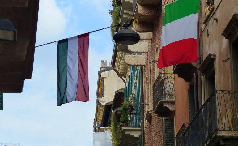 Nelle vie del centro sventolano le bandiere di Italia e Ungheria per l'imminente festival internazionale dei giochi di strada