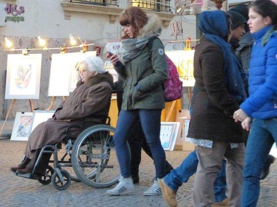 Anziana signora in carrozzina una domenica in Piazza Bra