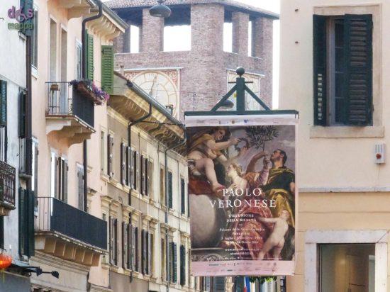 Manifesto della mostra su Paolo Veronese in via Roma a Verona, con Castelvecchio sullo sfondo