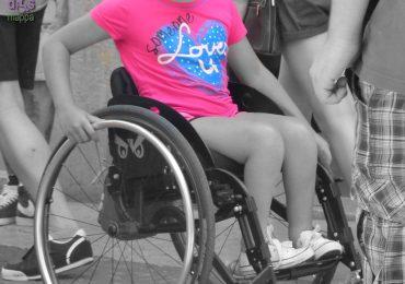 Piccola turista tedesca in carrozzina incontrata in via Cappello a Verona con t-shirt rosa con scritta someone loves u