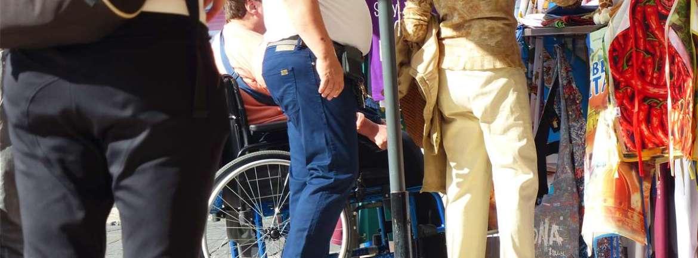 Turista disabile in carrozzina tra le bancarelle di Piazza delle Erbe