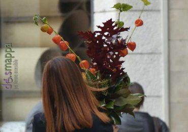 Vista in via Oberdan a Verona, donna con questa composizione floreale ispirata all'autunno in cui spicca il ramo con le belle bacche di alkekengi