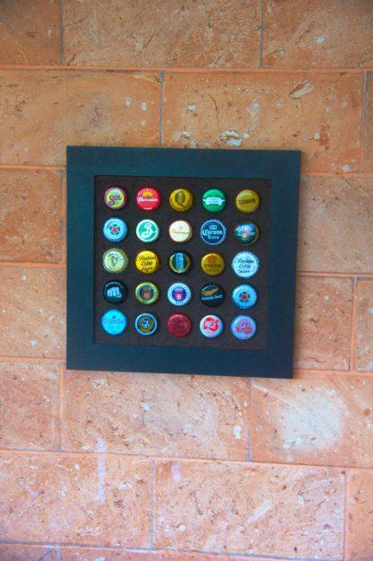 Painel decorativo quadrado para 25 tampinhas em MDF usinado com acabamento laminado preto.