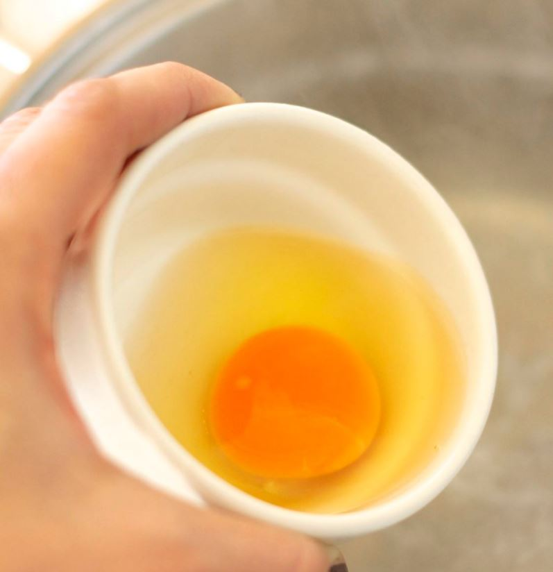 uovo crudo in una ciotola, pronto per essere versato in acqua