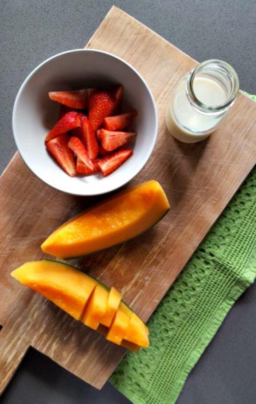 tagliere con una ciotola di fragole e una fetta di melone tagliata a cubetti