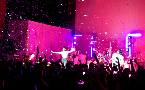 Janelle Monae performs on stage with her band as confetti falls on the audience.