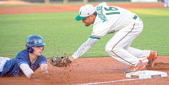 Miami third-baseman Edgar Michelangeli looks to tag out a Tar Heel at third base in Miami's 10-4 win Friday / Hurricanesports