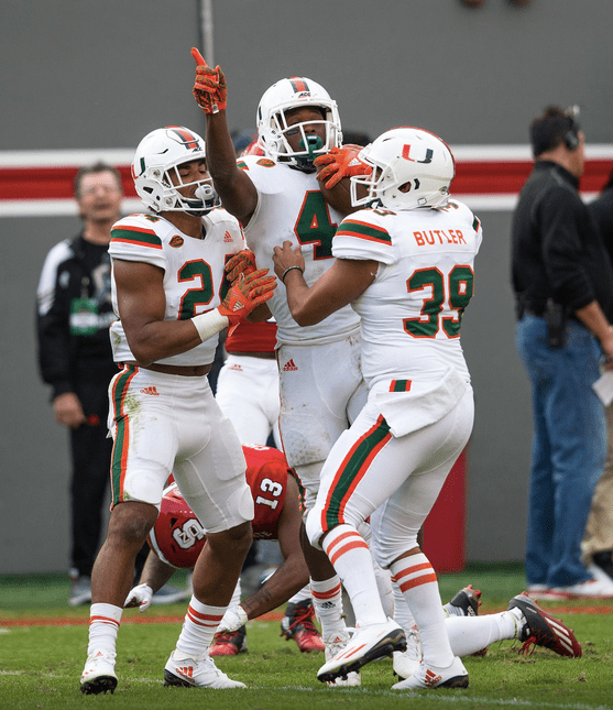 Miami's Jaquan Johnson (4) celebrates with teammates Travis Homer (24) and Jordan Butler (39) after recovering a fumble against NC State Saturday in Raleigh, N.C. (hurricanesports)