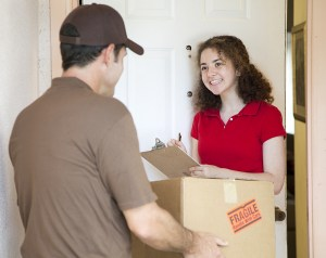 bigstockphoto_Young_Woman_Signs_For_Delivery_6316259