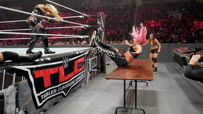 Ruby Riott puts Liv Morgan of Ruby Riott's Squad through a Table as Sarah Logan looks on in horror at WWE TLC