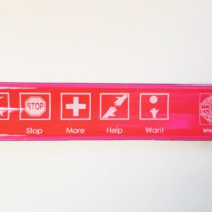Red slap bracelet with symbols for yes, no, stop, more, help and want as well as the FDM logo
