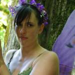 A hapa woman looking away wearing a purple flower crown, purple wings and a green dress standing against a tree