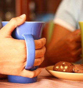 Friends Meeting And Enjoying Coffee And Cookies