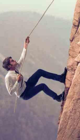 Homem escalando montanha vestido terno e gravata