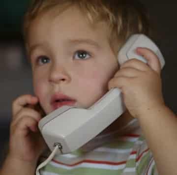Menino triste ao telefoe