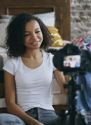 Moça gravando vídeo. Morena com camiseta branca e cama atrás
