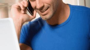 Freelancer sorrindo ao celular com camisa azul notebook e café na xícara