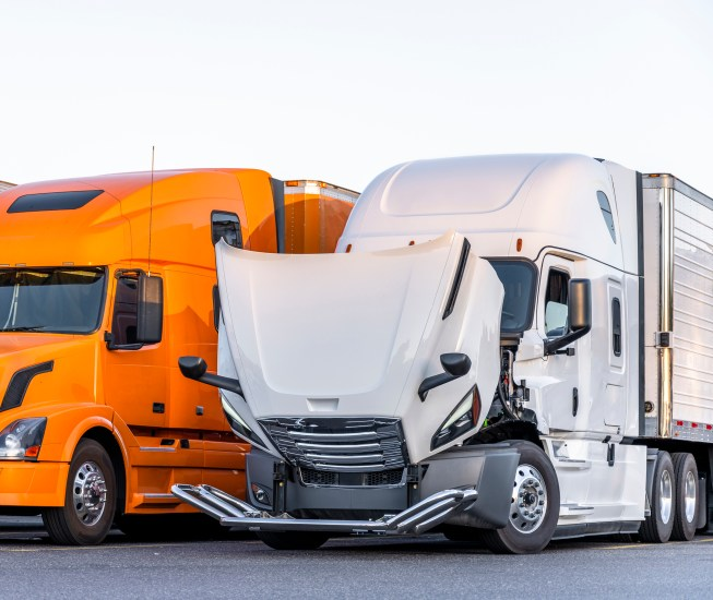 White bonnet big rig semi truck with open hood for engine inspection and possible mobile repair standing on the truck stop parking lot on row with another semi trucks