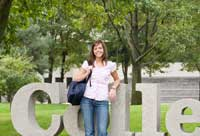 student leaning against college sign representing summer college admission prep tips