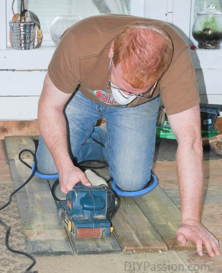 Use a belt sander to fix up reclaimed fence posts