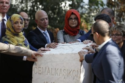 Hatice Cengiz, center, the fiancee of slain Saudi journalist Jamal Khashoggi, colleagues and friends of  Khashoggi, including Washington Post and Amazon owner Jeff Bezos, unveil a plaque near the Saudi Arabia consulate in Istanbul, Turkey, marking the one-year anniversary of Khashoggi's death.