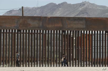 FILE - People walk along a border wall in El Paso, Texas, July 17, 2019.