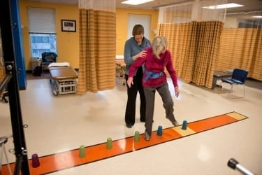 Michelle Brown, D.P.T., leads a patient through a balance exercise